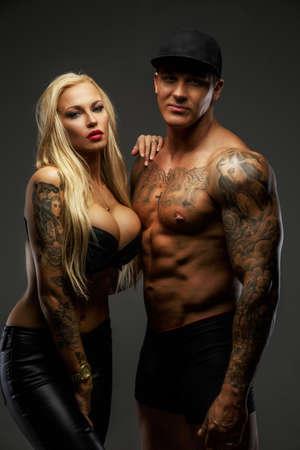 shirtless: Pareja moderna con cuerpos tatuados posando en el estudio Foto de archivo