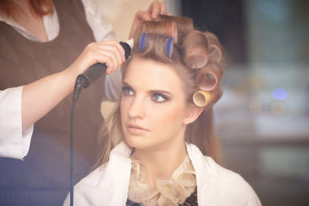 hairdressing: Blond female in hair salon. Hairdresser on background