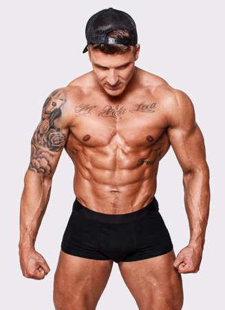 hombre desnudo: Bodybuilder con tatuajes aislado en fondo blanco