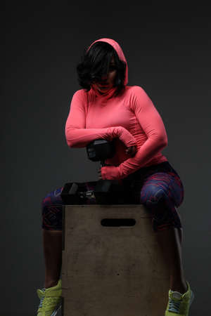 sudio: Attractive fitness woman in sportswear posing with dumbells in sudio on grey background