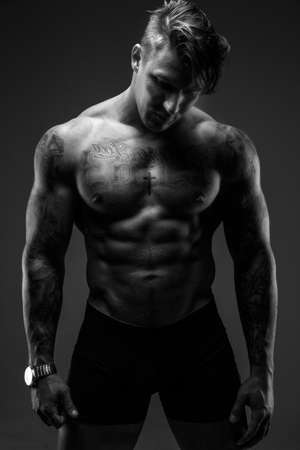 Black and white shoot of muscular man with tattooes.
