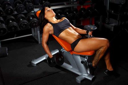 muskeltraining: Fitness woman in sexy Sportbekleidung macht Übungen in einem Fitness-Studio Lizenzfreie Bilder