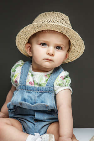 Beautiful child in jeans dress an summer hat on grey background photo