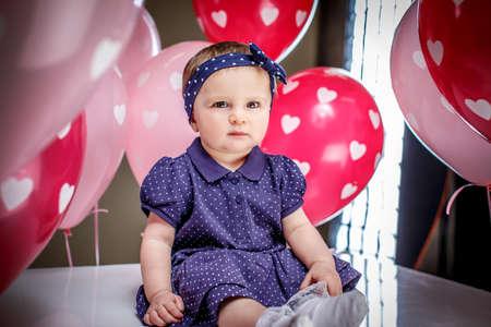 blue dress: Cute little girl in blue dress posing on balloons background Stock Photo