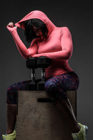 Attractive fitness woman in sportswear posing with dumbells in sudio on grey background