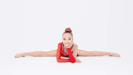 Flexible little girl in red dress doing gymnastic exercises on white background 免版税图像