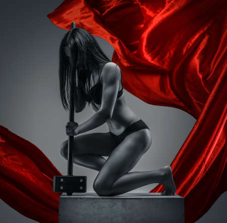 naked girl black hair: Attractive woman in underwear standing on one knee and holding big hummer. Red cloth on grey background
