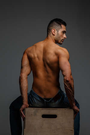 nude back: Guy with naked torso sitting on a podium. View from back. Grey background