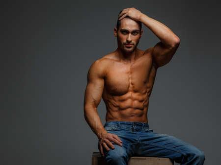 desnudo masculino: Chico muscular atractivo descamisado en pantalones vaqueros azules sentado en el podio en el fondo gris Foto de archivo