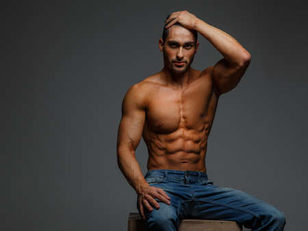 nude male: Shirtless attractive muscular guy in blue jeans sitting on podium on grey background