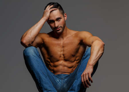 nude fashion model: Shirtless attractive muscular guy in blue jeans sitting on podium on grey background