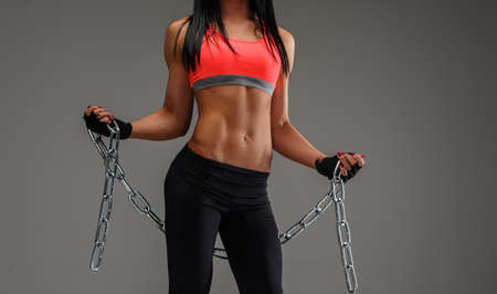 fit girl: Body of fitness woman in sportswear holding chain. Isolated on grey background