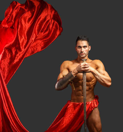 Muscoloso gladiator di sesso maschile con la spada in azione su sfondo grigio