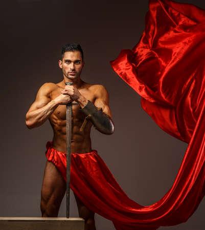 shirtless guy: Individuo descamisado que sostiene swort. Pa�o rojo aislado sobre fondo gris Foto de archivo