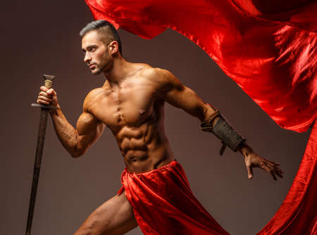 roman soldiers: Maschio senza camicia in armatura romana con la spada in movimento. Panno rosso su sfondo grigio Archivio Fotografico