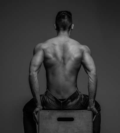 Guy with naked torso sitting on a podium. View from back. Grey background