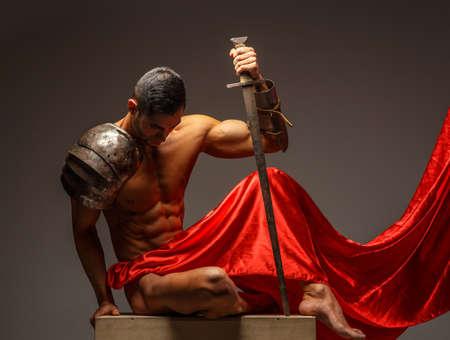 guerrero: Guerrero Roma sentado en el podio y mirando hacia abajo. Aislado en el fondo gris Foto de archivo