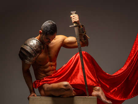 Roma guerriero seduto sul podio e guardando verso il basso. Isolato su sfondo grigio