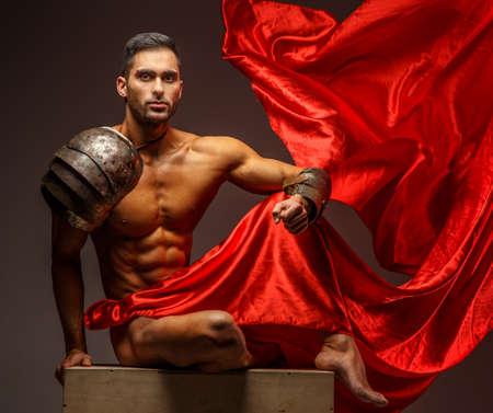 uomo rosso: Uomo muscolare senza camicia seduto su un podio. Panno rosso su sfondo grigio Archivio Fotografico