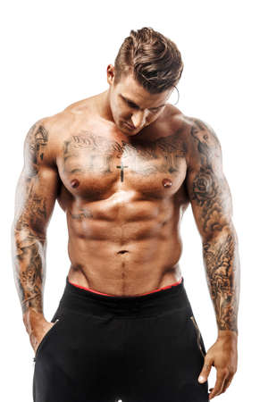 문신 된 근육 질의 남자 스튜디오에서 포즈입니다. 흰 배경에 고립