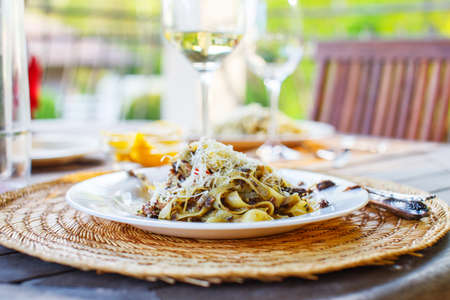 Glass of white wine and dish with pasta