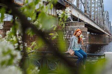 green leafs: Redhead girl posing near old train bridge. Shoot throught green leafs
