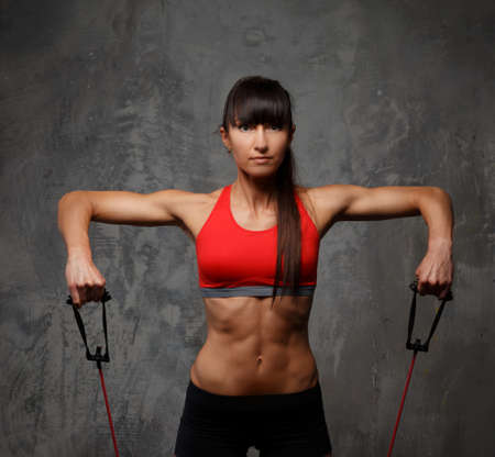 expander: Athletic woman in sportswear doing exercises with expander Stock Photo
