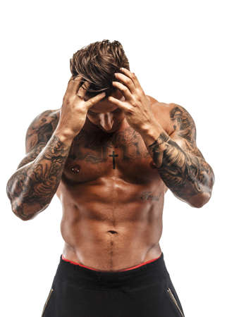 Muscular tattooed shirtless guy isolated on white background