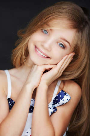 Cute smilling girl with blue eyes. Isolated on dark background.