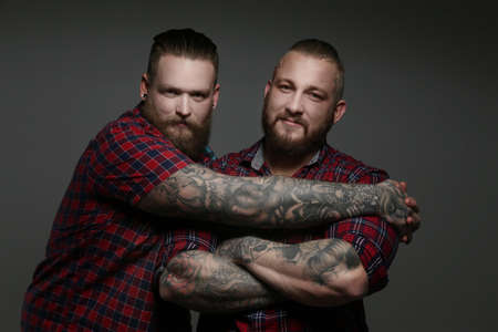 beefcake: Two guys in red shirts with beards and tattoos. Isolated on grey background