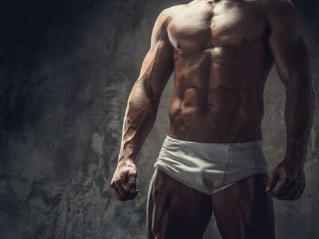 Muscular fitness model guy in white boxer posing on grey background.
