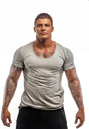 그의 손에 문신와 회색 t- 셔츠에있는 굉장한 녀석. 흰색 배경에 고립.