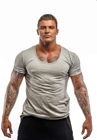 Awesome guy in grey t-shirt with tattoos on his hands. Isolated on white background.