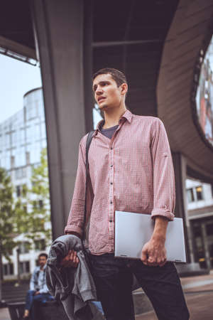 interactivity: Guy on the modern street in casual clothing with laptop