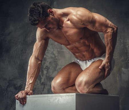 Bodybuilder guy posing on white podium on his knees. Isolated on grey background.