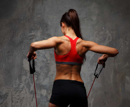 gym girl: Fitness foman from back doing exercises with expander.