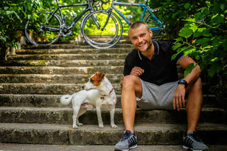 lovers park: Man with dog sitting on stairs. Bicycles on background.