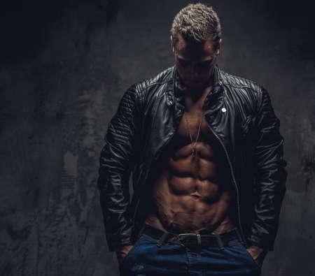 Gespierde man in blauwe jeans en zwarte jas droeg op shirtless lichaam. Geïsoleerd op grijze achtergrond. Stockfoto