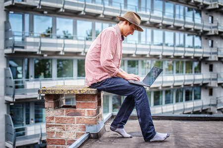 multifamily: Man in blue jeans and pink shirt sitting on the roof with laptop. Stock Photo