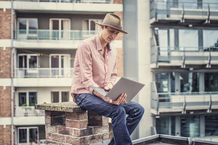 interactivity: Man in hat with laptop. Multifamilly houses on background.