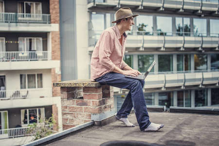 interactivity: Man in blue jeans and pink shirt sitting on the roof with laptop. Stock Photo