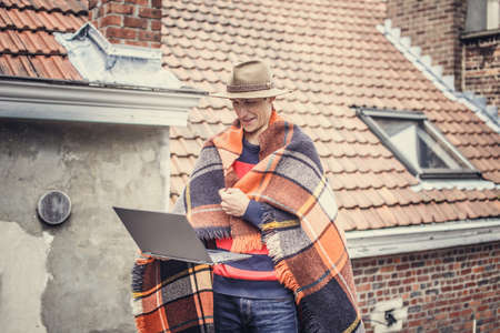 interactivity: Man with blanket on the roof. Stock Photo