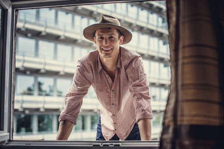 multifamily: Smiling guy in big hat looking through window.
