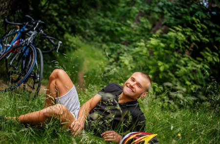 cycles: Smiling guy lying on grass. Cycles on background. Stock Photo