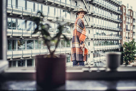 multifamily: Man in blanket on multifamily house background. Stock Photo
