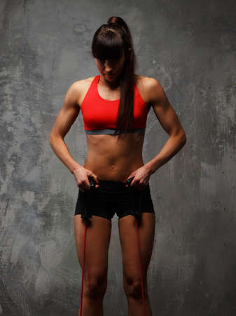 expander: Slim female in sportswear doing exercises with expander. Stock Photo
