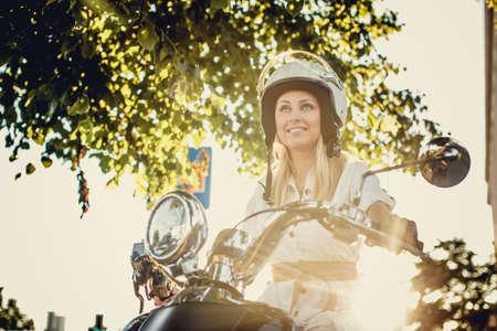 vestido blanco: Blond female in white dress and moto helmet sitting on scooter under green branches. Foto de archivo