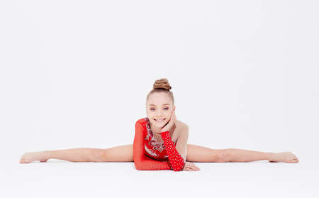 rhythmic gymnastics: Teenage girl in red dress doing gymnastic exercises on light background.