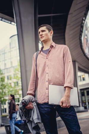 interactivity: Man in casual clothes holding laptop and posing on modern street.
