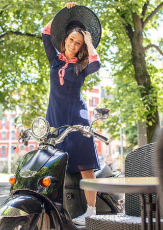 Fashin girl sitting on street scooter.